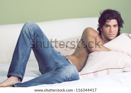 Young handsome man shirtless , embraced to pillow ,  in a sensual pose on bed.