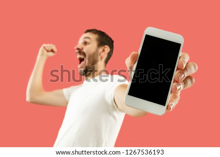 Young handsome man showing smartphone screen over coral background with a surprise face. Human emotions, facial expression concept. Trendy colors #1267536193
