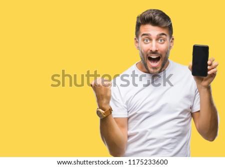 Young handsome man showing smartphone screen over isolated background screaming proud and celebrating victory and success very excited, cheering emotion