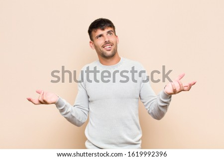 young handsome man shrugging with a dumb, crazy, confused, puzzled expression, feeling annoyed and clueless against warm wall