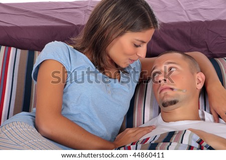 Young handsome man sick in  bed, thermometer in mouth.  Women nursing husband. Studio.