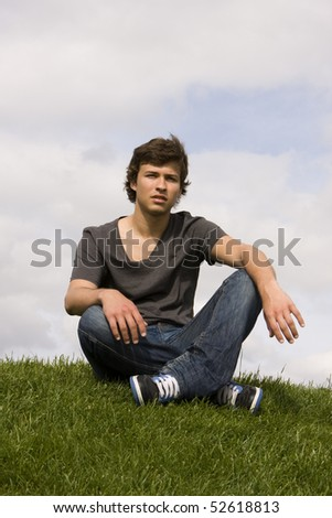Young handsome man sit on the grass