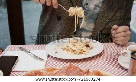 Stock Photo Young handsome man sitting at the table in cafe and enjoying the meal. Hungry male eating tasty pasta in restaurant.