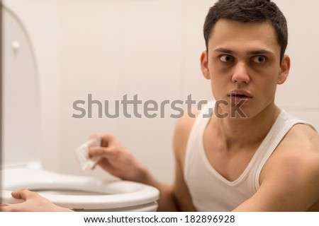 young handsome man sitting in toilet. drug addict alarmed and listening attentively