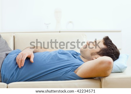 Young handsome man sleeping on couch at home, side view.