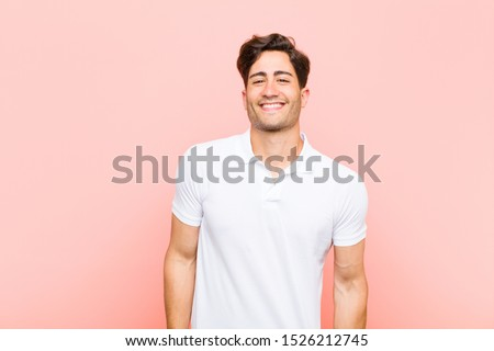 young handsome man smiling cheerfully and casually with a positive, happy, confident and relaxed expression against pink background