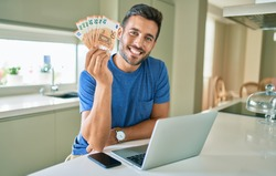 Young handsome man smiling happy holding euro banknotes at home