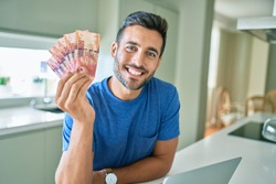 Young handsome man smiling happy holding south african rands banknotes at home