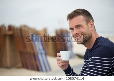 Young handsome man smiling with a cup of coffee in his hand at the beach. Wooden blue and white beach chairs in the background