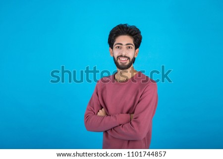 Young handsome man standing crossed arms on a blue background.