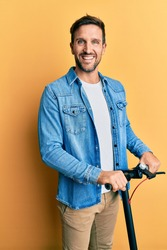 Young handsome man standing on modern scooter over yellow background looking positive and happy standing and smiling with a confident smile showing teeth