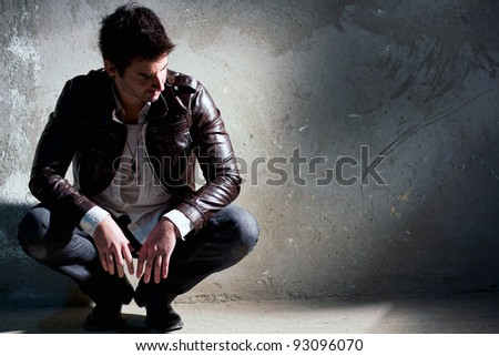 Young, handsome man thinking, sitting on the floor