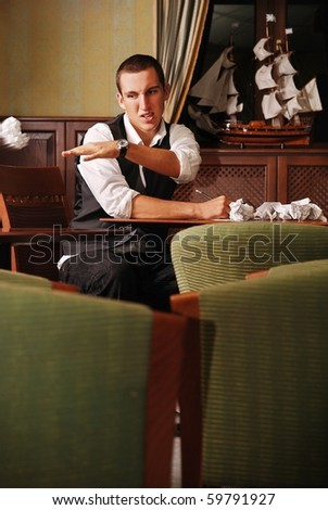 young handsome man throwing piece of paper desperately