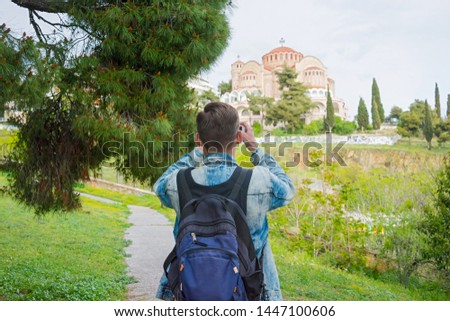 Young handsome man, tourist, with backpack taking pictures on a smartphone of the Church St. Paul in the in the Ano Poli in Thessaloniki, Greece.