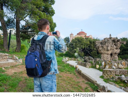 Young handsome man, tourist, with backpack taking pictures on a smartphone of the ruins in Pasha's Gardens and of the Church St. Paul in the in the Ano Poli in Thessaloniki, Greece.