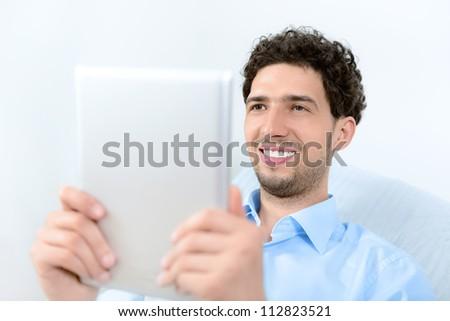 Young handsome man using a modern digital tablet. Studio shot.