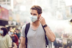 Young handsome man walking around night market in Taipei with backpack and wearing a face pollution mask to protect himself from the coronavirus.