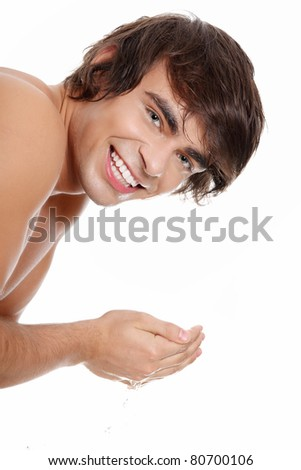 Young handsome man washing his face, isolated on white