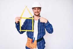 Young handsome man wearing architect hardhat holding build project smiling happy pointing with hand and finger