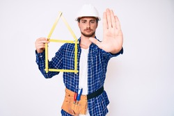 Young handsome man wearing architect hardhat holding build project with open hand doing stop sign with serious and confident expression, defense gesture