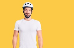 Young handsome man wearing bike helmet puffing cheeks with funny face. mouth inflated with air, crazy expression.