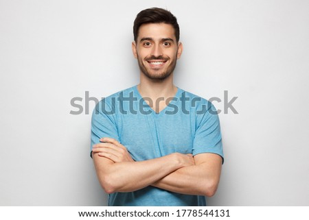 Young handsome man wearing blue tshirt, standing with crossed arms, isolated on gray background Foto stock ©