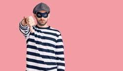 Young handsome man wearing burglar mask looking unhappy and angry showing rejection and negative with thumbs down gesture. bad expression.