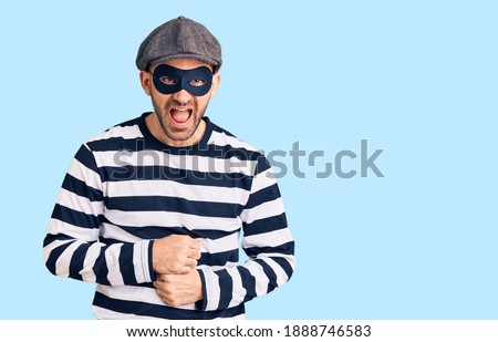 Young handsome man wearing burglar mask smiling and laughing hard out loud because funny crazy joke with hands on body.  Foto stock ©