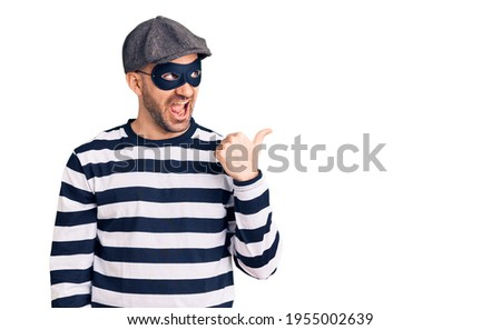 Young handsome man wearing burglar mask smiling with happy face looking and pointing to the side with thumb up.  Stockfoto ©