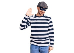 Young handsome man wearing burglar mask waiving saying hello happy and smiling, friendly welcome gesture