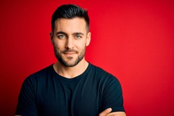Young handsome man wearing casual black t-shirt standing over isolated red background happy face smiling with crossed arms looking at the camera. Positive person.