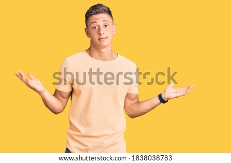 Young handsome man wearing casual clothes clueless and confused expression with arms and hands raised. doubt concept.