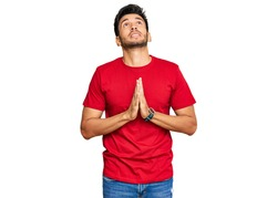 Young handsome man wearing casual red tshirt begging and praying with hands together with hope expression on face very emotional and worried. begging.