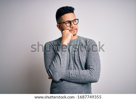 Young handsome man wearing casual sweater and glasses over isolated white background with hand on chin thinking about question, pensive expression. Smiling with thoughtful face. Doubt concept.