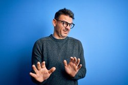 Young handsome man wearing casual sweater and glasses standing over blue background disgusted expression, displeased and fearful doing disgust face because aversion reaction. With hands raised