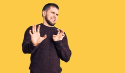 Young handsome man wearing casual sweater disgusted expression, displeased and fearful doing disgust face because aversion reaction. with hands raised
