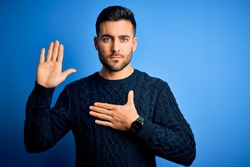 Young handsome man wearing casual sweater standing over isolated blue background Swearing with hand on chest and open palm, making a loyalty promise oath