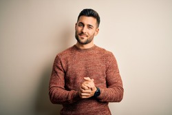 Young handsome man wearing casual sweater standing over isolated white background with hands together and crossed fingers smiling relaxed and cheerful. Success and optimistic