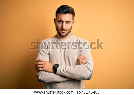 Young handsome man wearing casual sweater standing over isolated yellow background skeptic and nervous, disapproving expression on face with crossed arms. Negative person. Stock foto ©