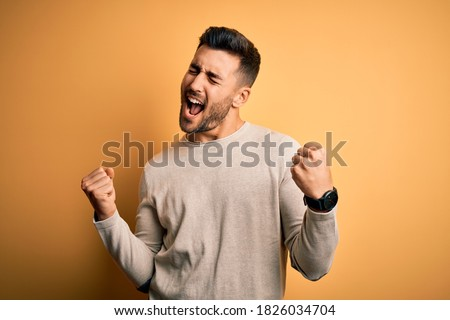 Young handsome man wearing casual sweater standing over isolated yellow background very happy and excited doing winner gesture with arms raised, smiling and screaming for success. Celebration concept.