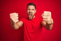 Young handsome man wearing casual t-shirt over red isolated background angry and mad raising fists frustrated and furious while shouting with anger. Rage and aggressive concept.
