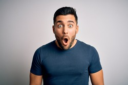 Young handsome man wearing casual t-shirt standing over isolated white background afraid and shocked with surprise expression, fear and excited face.