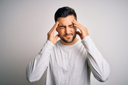 Young handsome man wearing casual t-shirt standing over isolated white background suffering from headache desperate and stressed because pain and migraine. Hands on head.