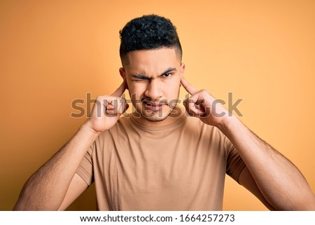 Young handsome man wearing casual t-shirt standing over isolated yellow background covering ears with fingers with annoyed expression for the noise of loud music. Deaf concept. ストックフォト ©