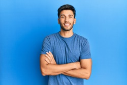 Young handsome man wearing casual tshirt over blue background happy face smiling with crossed arms looking at the camera. positive person.