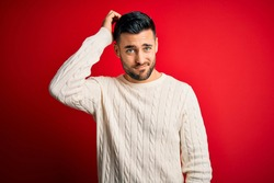 Young handsome man wearing casual white sweater standing over isolated red background confuse and wonder about question. Uncertain with doubt, thinking with hand on head. Pensive concept.