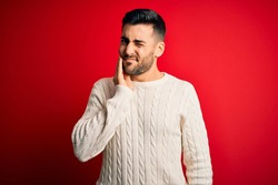 Young handsome man wearing casual white sweater standing over isolated red background touching mouth with hand with painful expression because of toothache or dental illness on teeth. Dentist