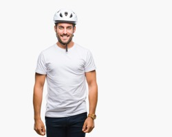 Young handsome man wearing cyclist safety helmet over isolated background with a happy and cool smile on face. Lucky person.