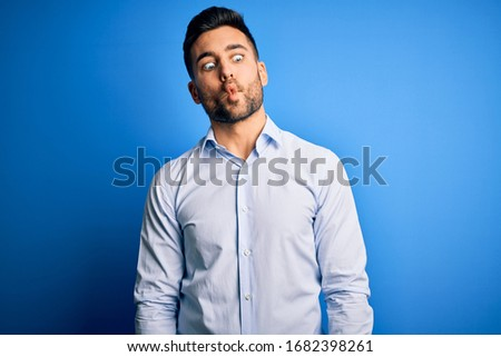 Young handsome man wearing elegant shirt standing over isolated blue background making fish face with lips, crazy and comical gesture. Funny expression.