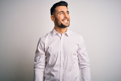 Young handsome man wearing elegant shirt standing over isolated white background looking away to side with smile on face, natural expression. Laughing confident.